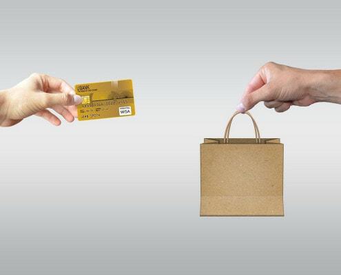 Zwei Hände tauschen eine Kreditkarte für eine Einkaufstüte